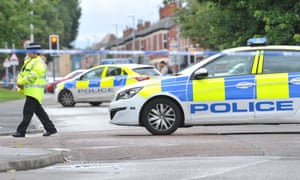Police at the scene of the stabbing in Moss Side, Manchester