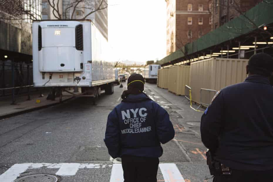 A worker from the Office of Chief Medical Examiner stands in front of a refrigeration truck outside Bellevue Hospital in New York.
