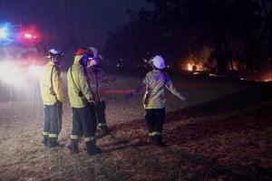 RFS crews fight a fire at the Green Wattle Creek fire near Bargo NSW tonight as it starts to rain. Mikaela Kramer from the Glenbrook-Lapstone dances in the rain 21st December 2019.