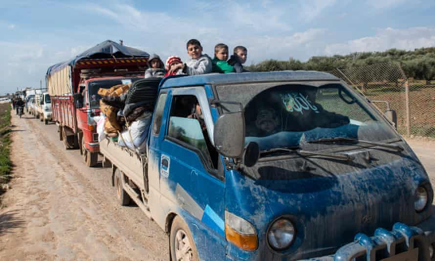 A displaced family ride in the back of a truck.