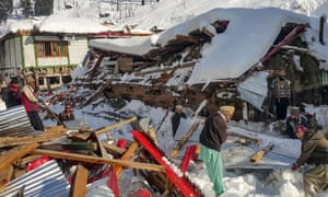 Locals remove debris from a house flattened by an avalanche in Kashmir's Neelum Valley