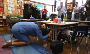 The San Francisco mayor, London Breed, ducks under a desk with elementary school students during a drill last year.