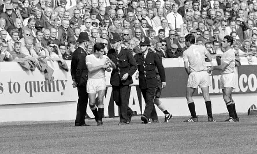 Uruguay's Héctor Silva is escorted from the pitch by policemen after being sent off during the World Cup quarter-final with West Germany at Hillsborough.