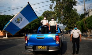 Police officers wearing face masks wave the Guatemalan flag from a police truck on the streets of the Chacara neighborhood during a partial curfew ordered by the government, in Guatemala City on 27 March.