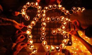 Indian Sikh devotees light candles around the view of 'Ek Om Kar' in Amritsar