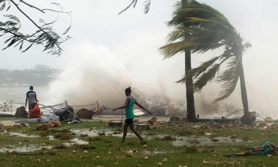 Port Vila residents walk past debris from Cyclone Pam near the waterfront.