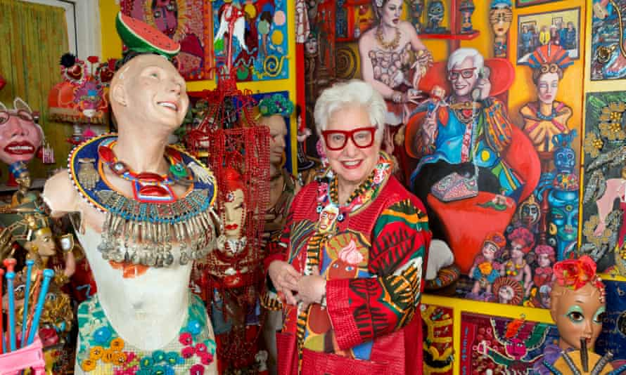 Artist Sue Kreitzman in huge glasses and an ethnic top next to a mannequin with necklaces and walls lined with her self-portraits