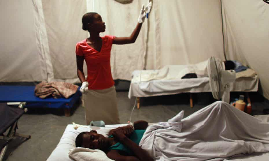 Nurse Ruth Saint Aimé helps Jeff Louissait as he lies on a cot while being treated for cholera in the German Red Cross cholera treatment facility on 22 November 2010 in Archaie, Haiti.