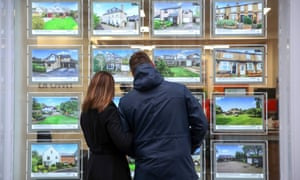 A couple look at houses for sale in the window of an estate agent