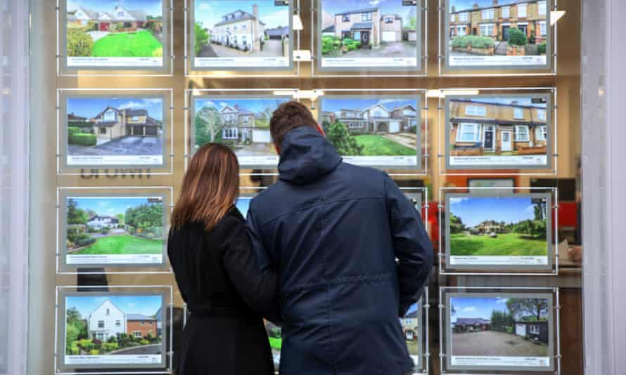Couple look at pictures in estate agent's window