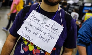 Photograph of a man wearing a sign reading 'please stand back: I've updated my privacy policy and terms of service'