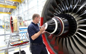 An employee fits the nose cone to a Trent 700 aircraft engine on the production line at the Rolls-Royce Holdings Plc factory in Derby, U.K., on Wednesday, Aug. 19, 2015.