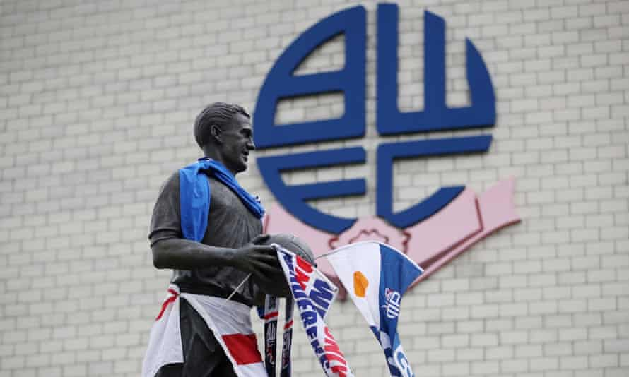 The statue of Nat Lofthouse outside Bolton's stadium on Tuesday, bedecked by anxious supporters