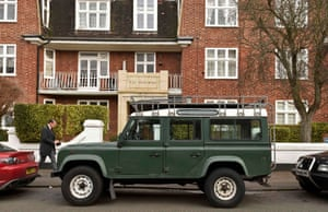 A man passes a Land Rover Defender parked in London