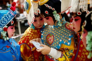 Beijing, ChinaA participant plays a game on her phone as others watch during a break in a traditional Chinese opera competition at the National Academy of Chinese Theatre Arts