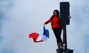 A protester wearing a yellow vest stands above the crowd on a traffic light on the Champs-Élysées in Paris
