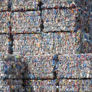 Bound bales of crushed plastic bottles and containers sit stacked ready to be recycled at a recycling centre.
