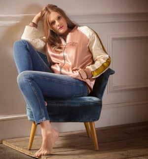 Romola Garai sitting on a chair wearing a pink bomber and jeans