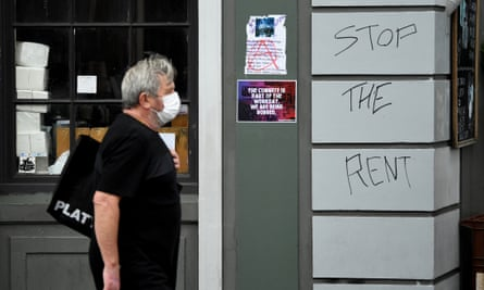 A man walks past a sign saying Stop the Rent on King Street in Newtown in Sydney, March 23, 2020.