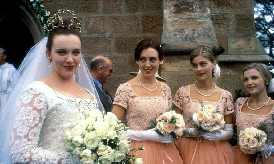 Muriel in a wedding dress with her bridesmaids