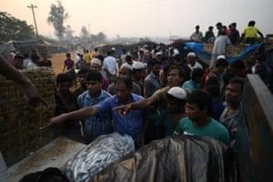Rohingya refugees gesture to Bangladeshi fish sellers at the dawn fish market in Kutupalong refugee camp