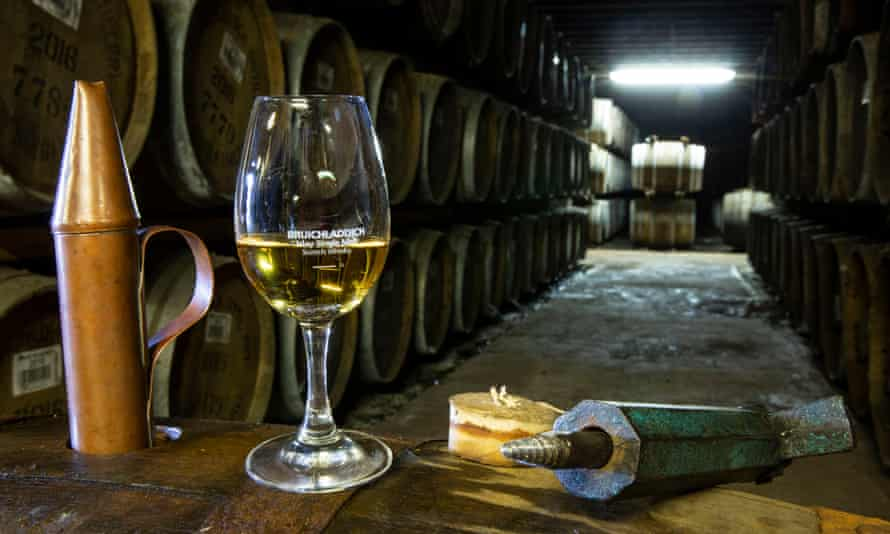 A whisky tasting glass and barrels