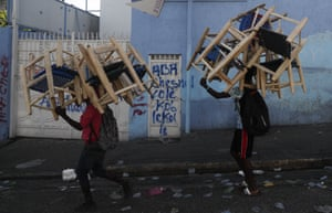 Port-au-Prince, Haiti: chair vendors walk past a street market where businesses have closed in recent days as protesters call for President Jovenel Moïse to resign