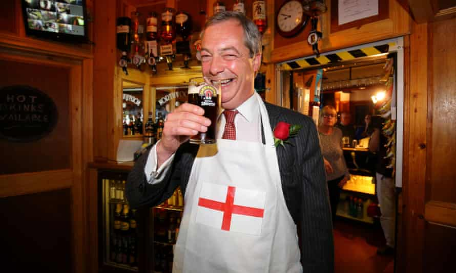 Nigel Farage grins with a pint in his hand and a St George's cross apron over his suit