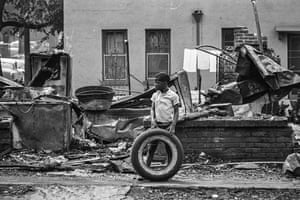 A child plays with a tyre in a black neighbourhood scarred by the rioting in Birmingham, Alabama