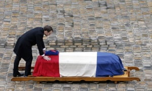 Emmanuel Macron touches the flag-draped coffin of Arnaud Beltrame, the gendarme who died after trading places with a woman during a hostage situation in Trèbes.