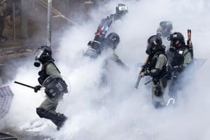 Riot police move through teargas