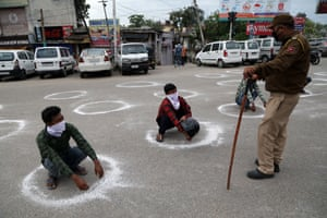 Jammu and Kashmir police officers force people to crouch inside a marked circle to maintain a minimum social distance after they allegedly violated Section 144 (gathering of more than three people) during the coronavirus lockdown