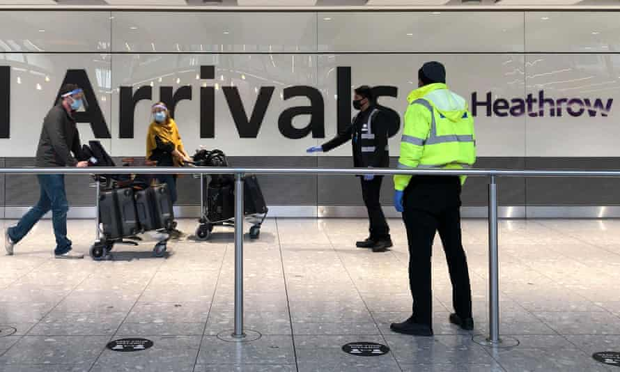 Passengers are escorted through the arrivals area of terminal 5 towards coaches destined for quarantine hotels, after landing at Heathrow airport on 23 April, 2021 in London, England.