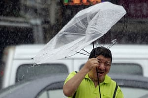 Taipei, Taiwan: A man holds an umbrella against powerful gusts of wind generated by Typhoon Lekima