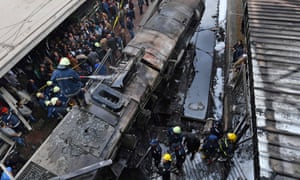 Firefighters at the scene of the crash at Ramses station in Cairo, Egypt