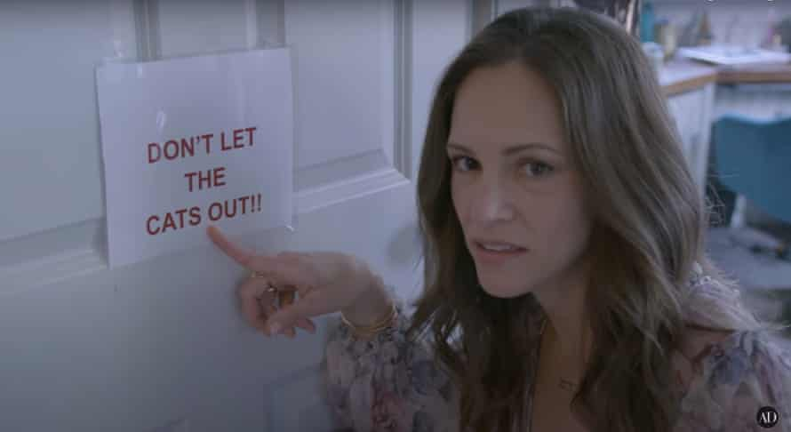 Susan Downey points to a laminated sign that reads: don't let the cats out