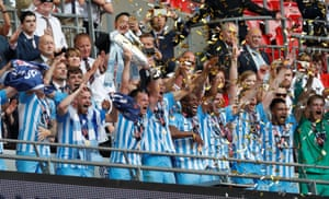 The Coventry City players celebrate with the trophy.