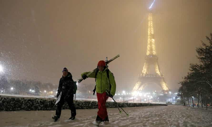 Men walk with skis on a snow-covered path near the Eiffel Tower in Paris
