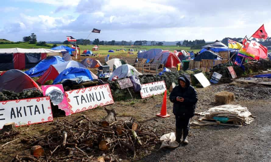 A woman collects firewood at Ihumātao