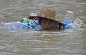 A flood-affected resident swims in floodwaters at Kyaut Ye village
