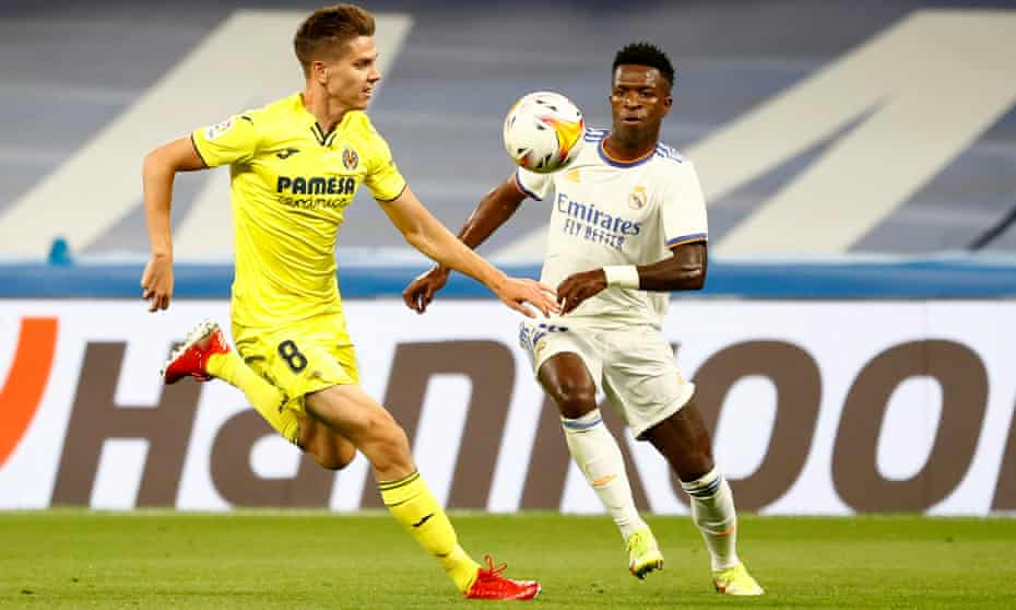 Real Madrid's Vinícius Júnior and Villarreal's Juan Foyth compete for the ball.