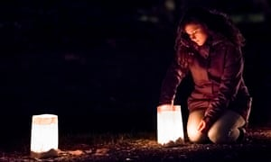 Young Woman lights lantern in paper bags at dark night,