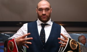 Tyson Fury poses with his belts.