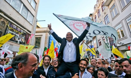 António Costa is raised in the air by crowd waving flags