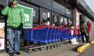 Workers use shopping trolleys to block the entrance to a Carrefour supermarket in Brussels