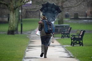 Wind catches an umbrella in the grounds of Winchester cathedral in Hampshire