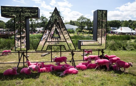 Pink sheep relax beneath the Latitude sign.
