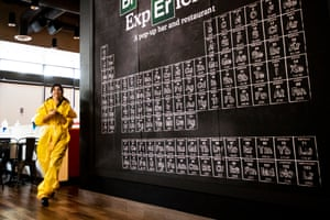 A waitress passes by the iconic periodic table from the TV series
