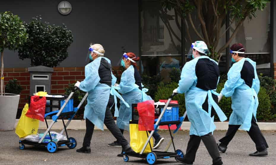 Healthcare workers don surgical masks before entering the Arcare aged care facility in Melbourne on Tuesday morning.
