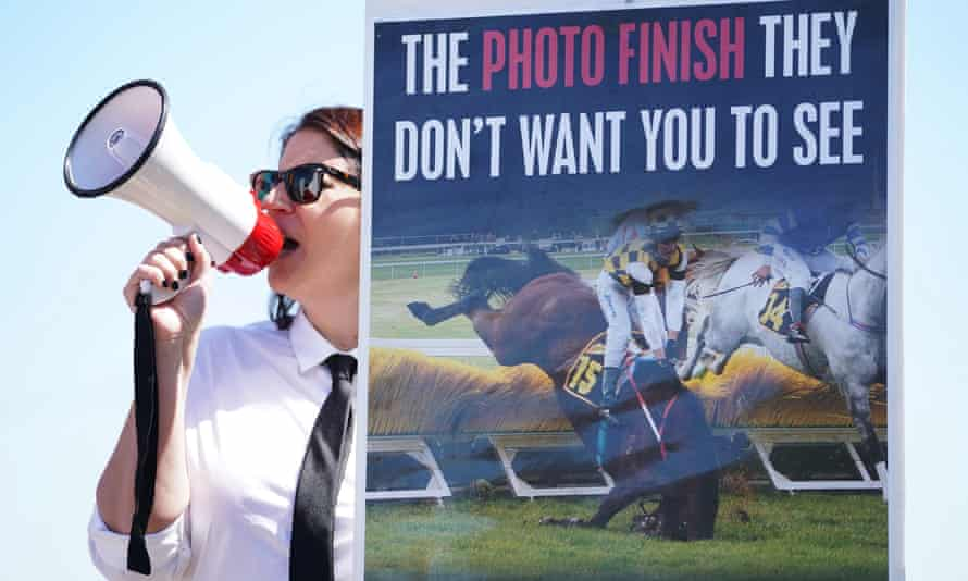 An animal rights activist with a loudhailer stands next to a poster  showing a horse breaking its leg in a race